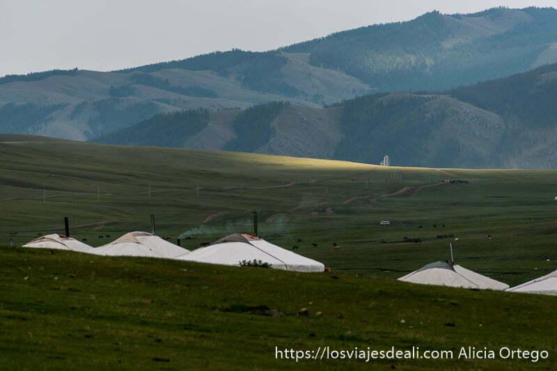 techos de gers con chimeneas echando humo enmedio de estepa cubierta de hierba y montañas al fondo en mongolia central