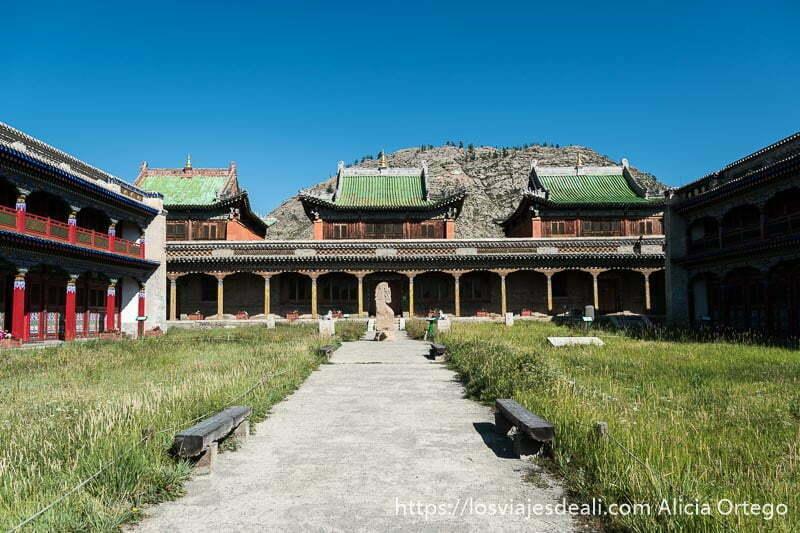 patio principal del monasterio de tsenserleg con tres edificios con tejados verdes de frente y una piedra con grabados en el centro