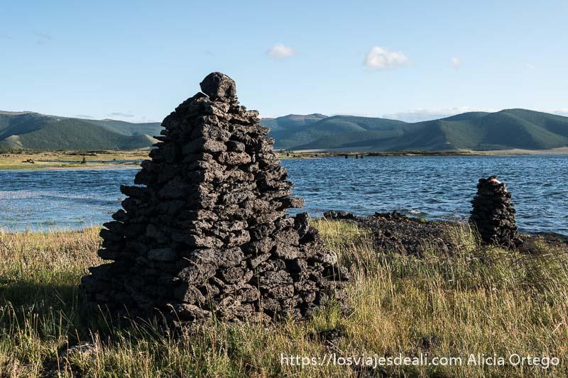 túmulos de piedra volcánica con forma de conos y el lago blanco detrás