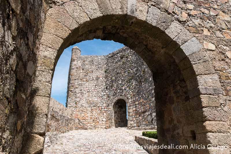 puerta de piedra con arco que da paso a pequeño patio con otra muralla y puerta arcada