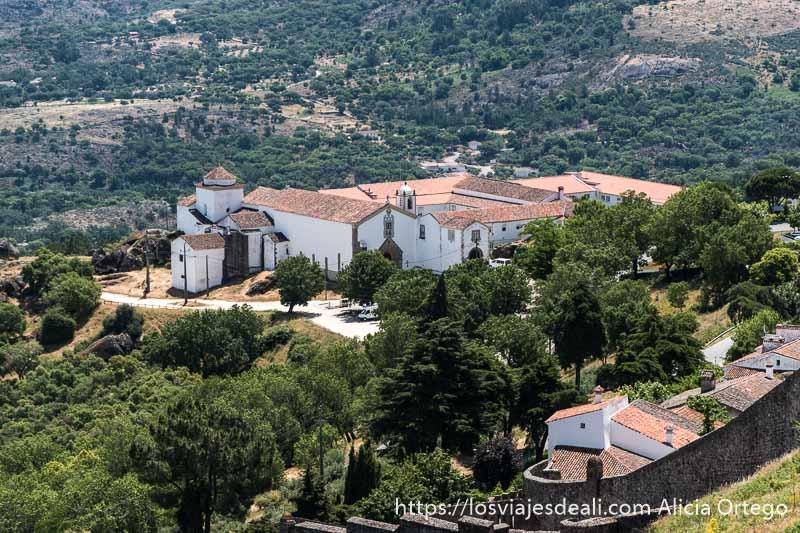 vista del convento qu ehay en la parte baja de marvao con edificios de color blanco y tejado de tejas rojas