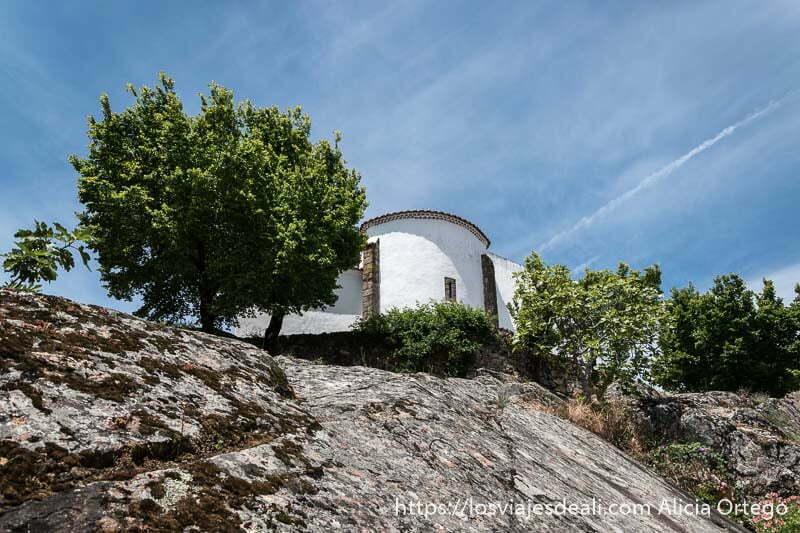 roca y árboles y parte de una iglesia encalada en la parte superior