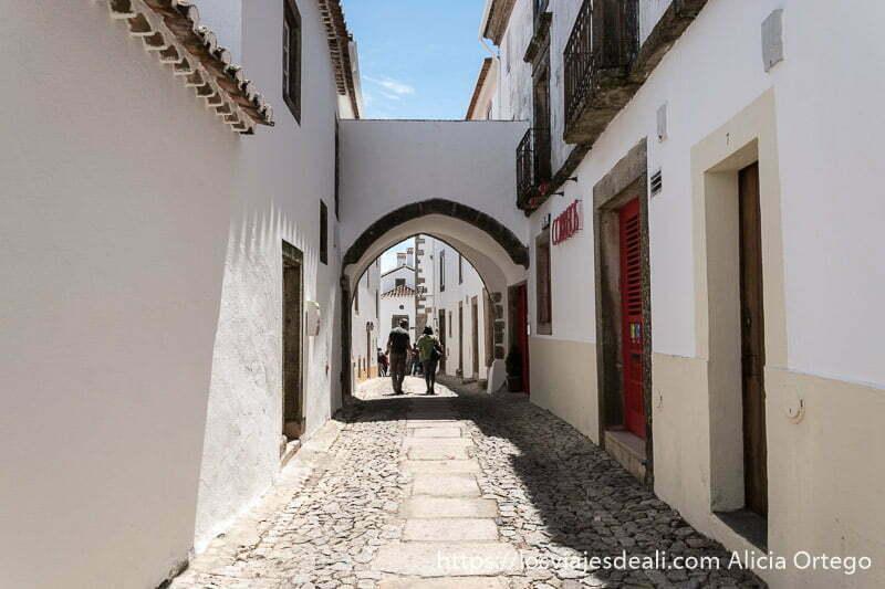 calle de Marvao con pequeño pasaje en forma de arco de contrapunto y dos personas andando en el fondo de la foto