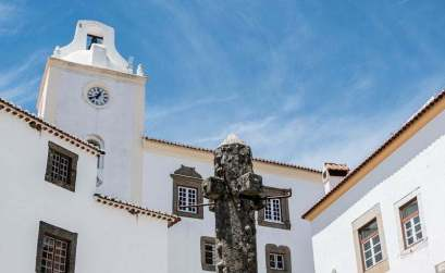 picota de piedra rodeada de casas blancas con ventanas de piedra y torre de iglesia con reloj en marvao portugal