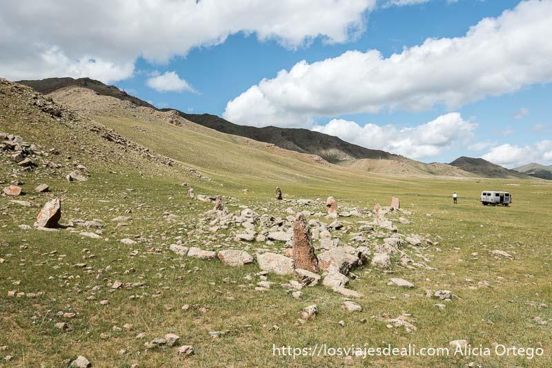 tumba neolítica con piedras formando cuadrado y piedras verticales en las cuatro esquinas y montañas en el lado izquierdo con nubes blancas en el cielo en un lugar de mongolia