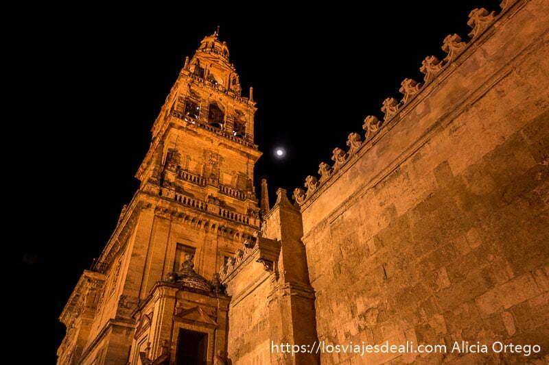 torre campanario de la mezquita iluminada por la noche con la luna llena al lado visitar córdoba
