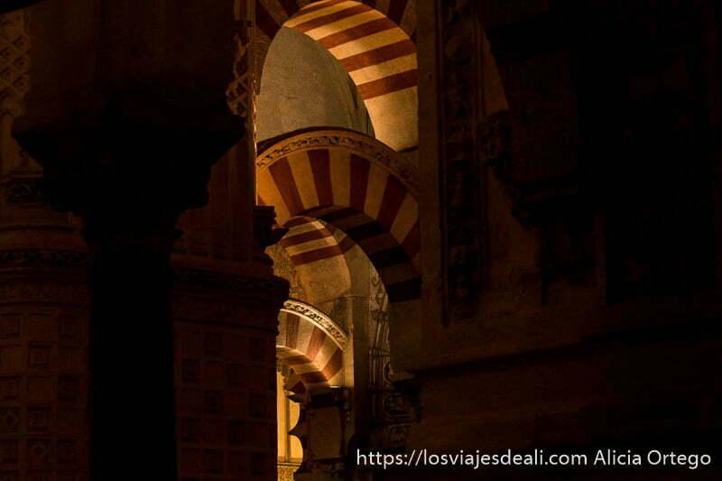 arcos estucados pintados de blanco y rojo óxido entre luces y sombras en el interior de la mezquita