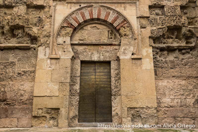 puerta exterior de la mezquita con arco en herradura muy antiguo y puerta de hierro