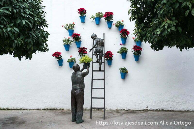 monumento a los patios de Córdoba con una estatua de un abuelo alzando una maceta a un niño que está subido a una escalera apoyada en pared con macetas con flores