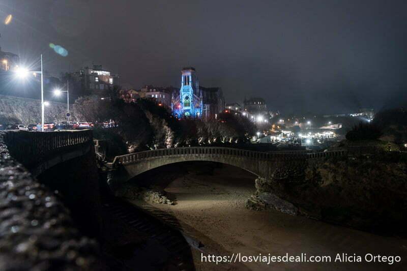 paseo junto al mar con puente de piedra y al fondo la iglesia san eugene iluminada por navidad en biarritz