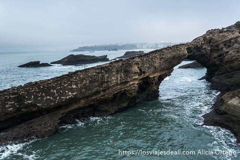 grandes rocas en el mar con forma de arco y detrás la costa con edificios de biarritz y el faro en otro saliente de roca