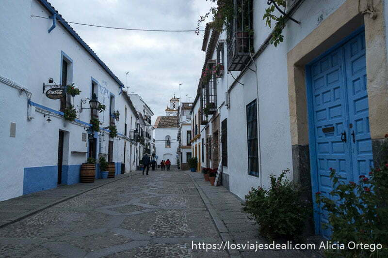 calle del barrio del alcázar viejo con casas blancas y zócalo azul y al fondo una iglesia