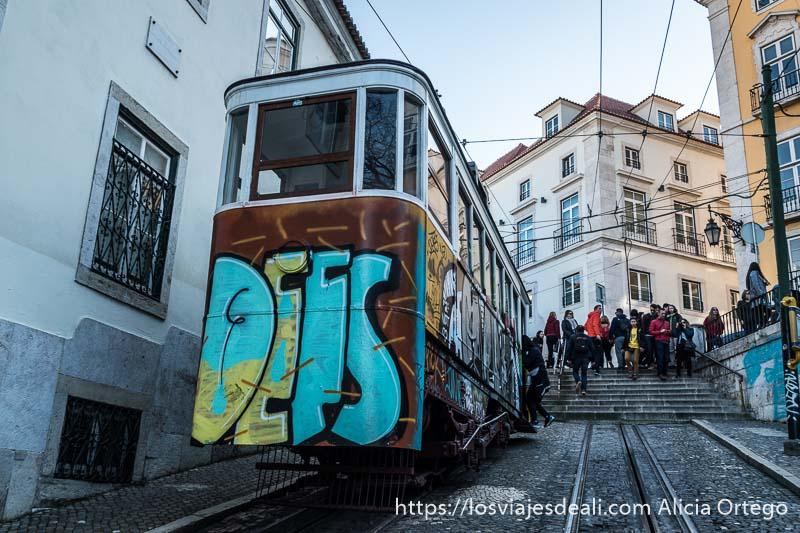 elevador de chiado pintado con grafitis y al fondo la gente que se acaba de bajar subiendo unas escaleras en el centro de lisboa