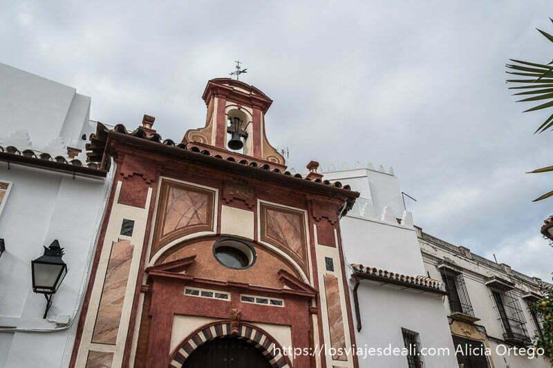 fachada de iglesia de córdoba pintada de colores ocres con una campana en la parte superior