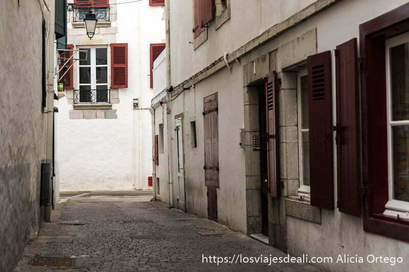 calle de san juan de luz con casas blancas con ventanas de madera rojas