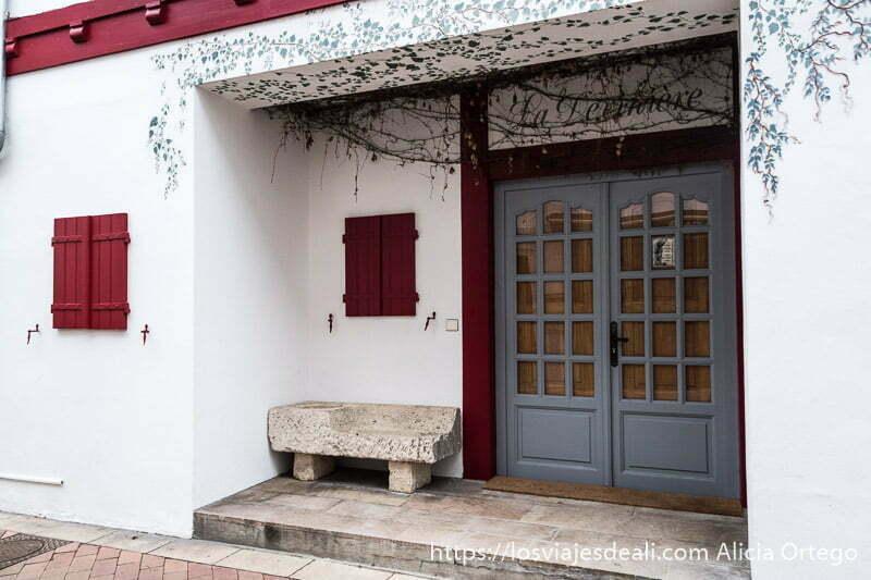 portal con pequeño banco de piedra y en la parte superior pintada en los muros una hiedra y ventanas de madera roja en la excursión a san juan de luz y biarritz