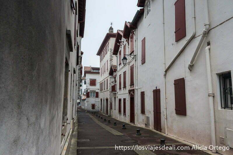 calle de casas blancas con ventanas y puertas de madera roja en la excursión a san juan de luz y biarritz