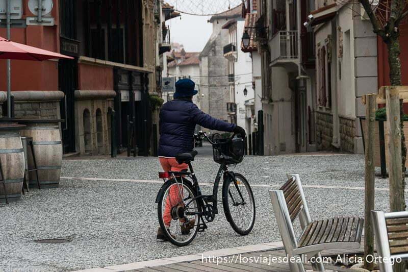 mujer abrigada empujando bicicleta con cesta en una calle de san juan de luz