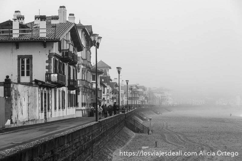 paseo de san juan de luz junto a la playa llena de niebla y a la izquierda casas típicas vascas y farolas