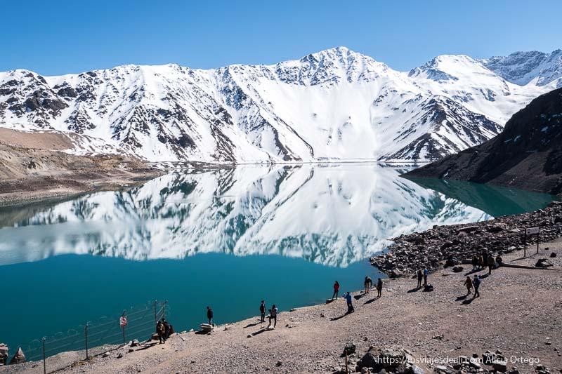 embalse de el yeso con montañas nevadas reflejadas en el abua y gente andando por la orilla en la escapada al cajón del maipo