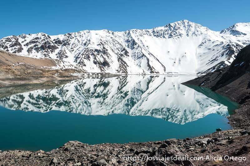 panorámica del embalse con la montaña nevada reflejándose en el agua en la escapada al cajón del maipo
