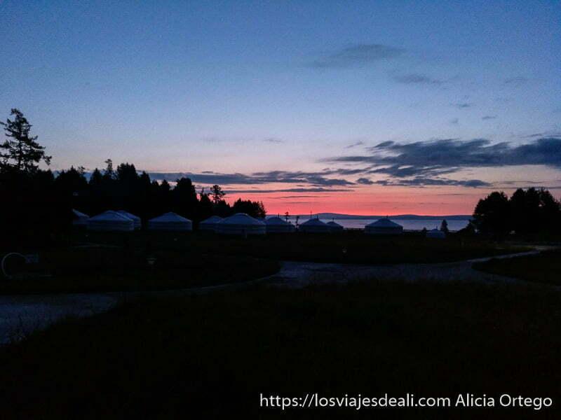 campamento de gers con lago khovsgol al fondo entre sombras con luz roja de atardecer en el horizonte