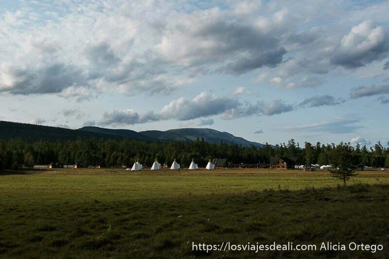 campamento con hilera de tipies de color blanco al fondo y detrás bosque y las montañas