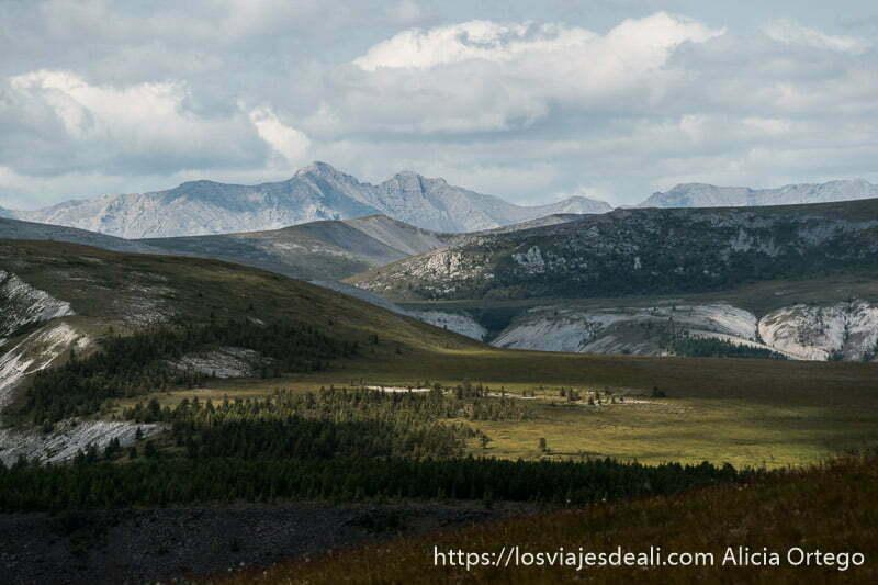 paisaje de montañas con dos picos muy altos al fondo, prados y bosquecillos en el lago khovsgol de mongolia