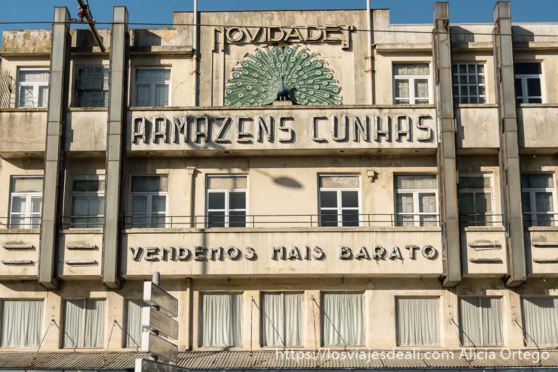 fachada de edificio modernista con cartel de unos almacenes de los años 70 y un pavo real como símbolo en oporto