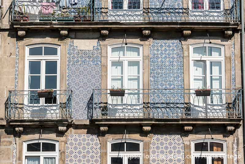 fachada con balcones de hierro y paredes con azulejos de distintos diseños en razones para viajar a oporto