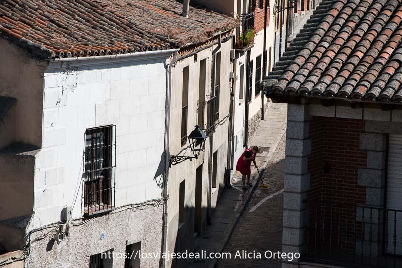 calle estrecha con una mujer barriendo en el centro de ávila