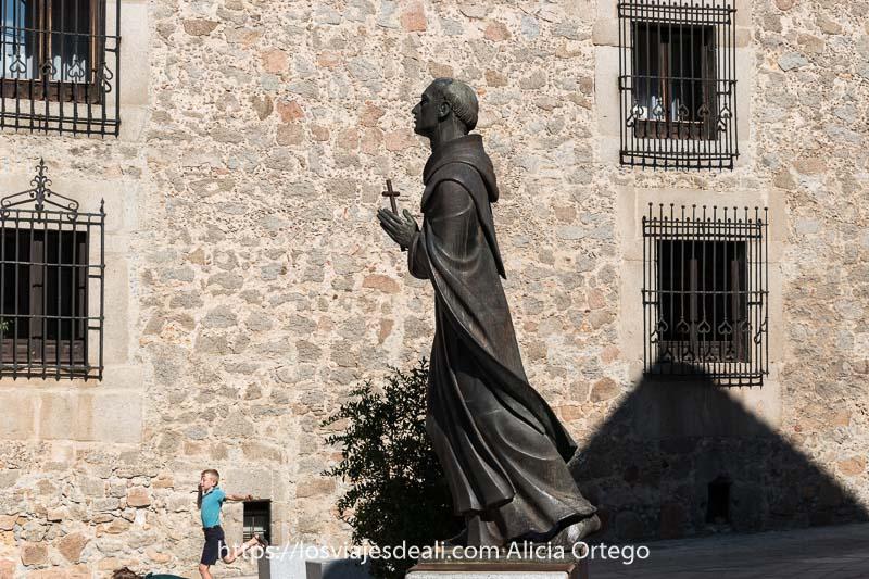 estatua de monje rezando con cruz en la mano en una plaza de ávila