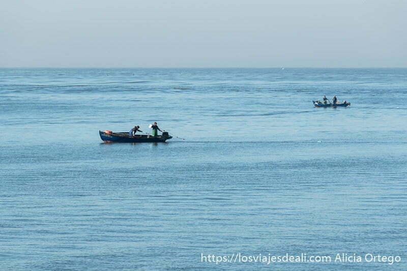 dos barcas de pescada cada una con dos personas recogiendo redes en el mar en foz do douro
