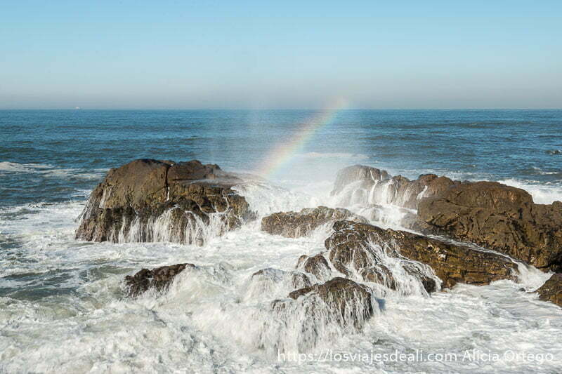 arco iris formado en el rastro de espuma de las olas que chocan contra un grupo de rocas en foz do douro