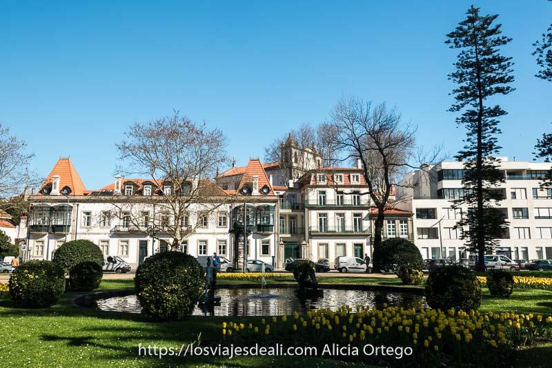 casas grandes con tejados rojos y un parque con tulipanes amarillos en primer plano y una fuente redonda en el centro