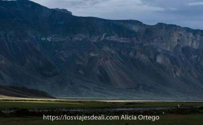 valle con gran montaña y luz del sol iluminando un camino verde uno de los amaneceres del mundo
