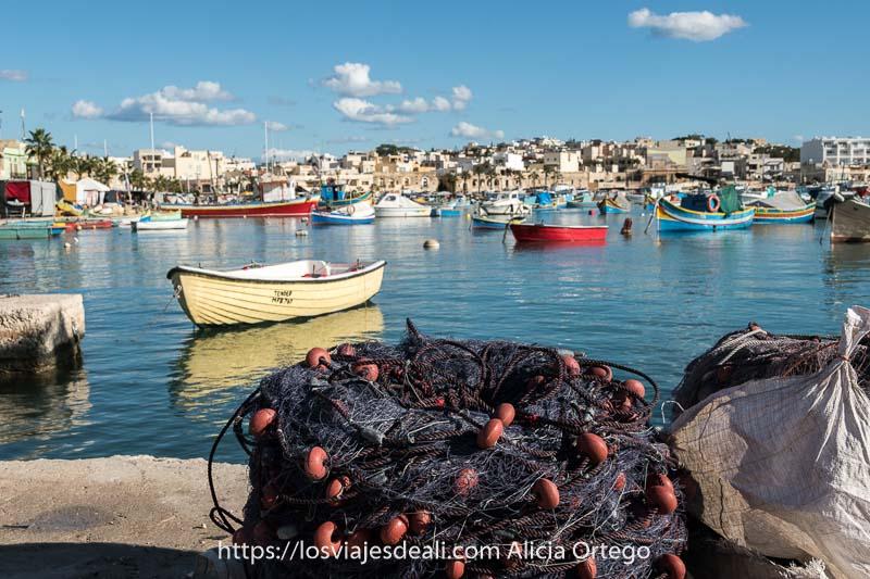 panorámica del puerto antiguo de Marksaxlokk con barcas de colores y en primer plano un montón de redes de pesca de color gris