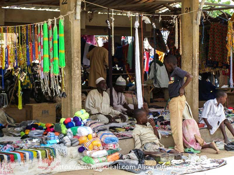 puesto del mercado africano de gorom gorom con abalorios y lanas de colores y varios niños sentados delante