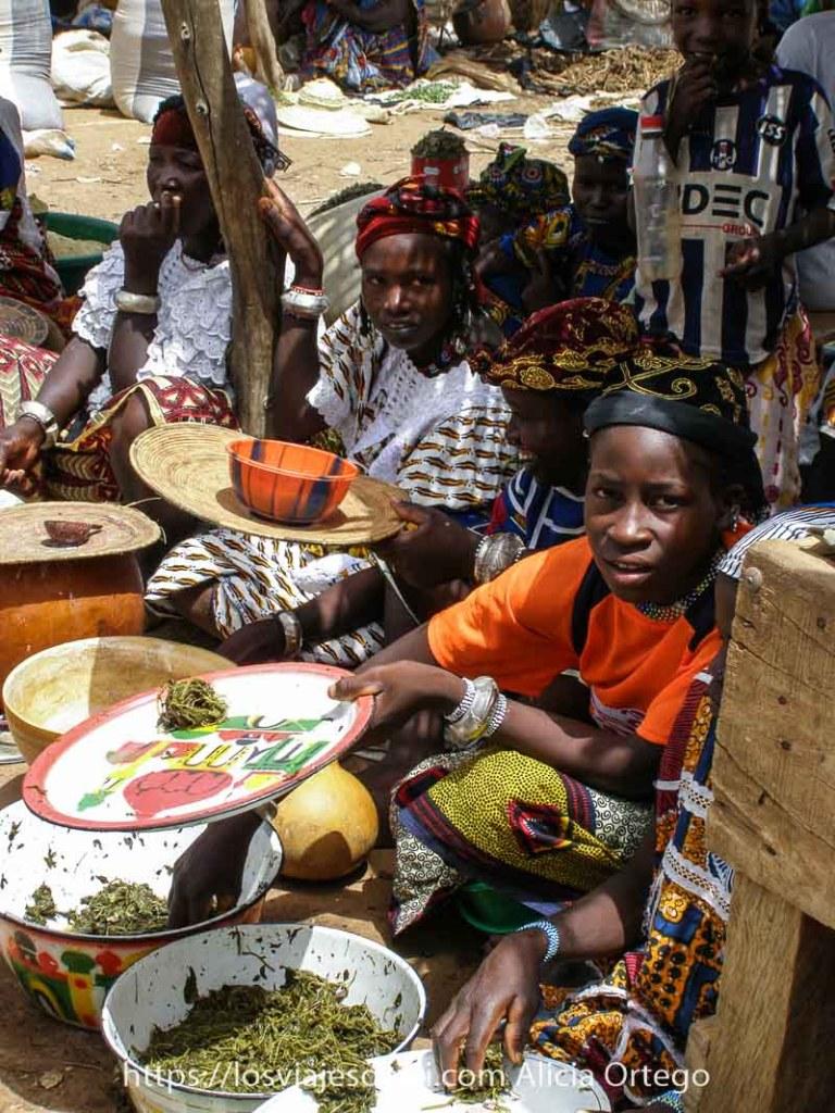 niñas sentadas en el suelo vendiendo verdura cocida en palanganas blancas en el mercado africano de gorom gorom