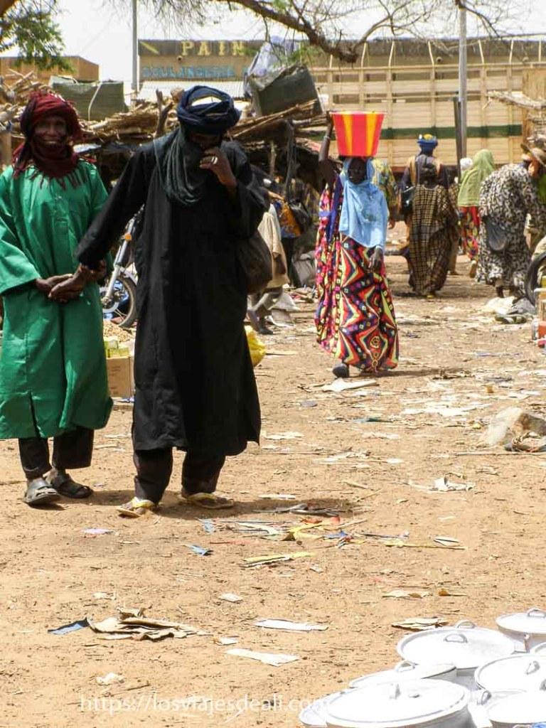 dos tuareg con turbante caminando por el mercado cogidos de la mano uno vestido de verde y el otro de negro y detrás mujer con barreño de plástico de colores en la cabeza en el mercado africano de gorom gorom
