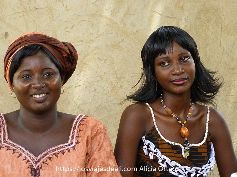 dos mujeres jóvenes con una pared de adobe de fondo. La de la derecha lleva el pelo liso y va muy maquillada y es guapísima