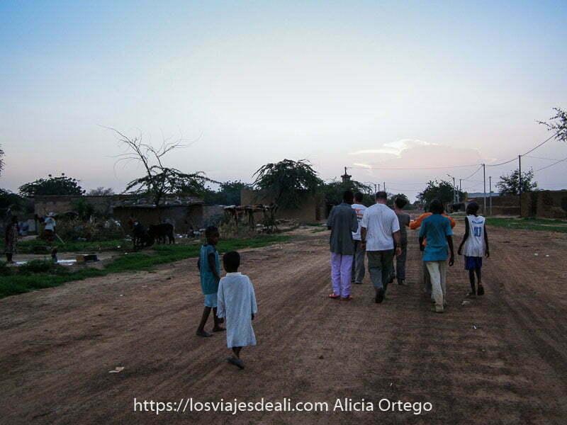 andando por la carretera de tierra en el atardecer rodeados de niños de gorom gorom