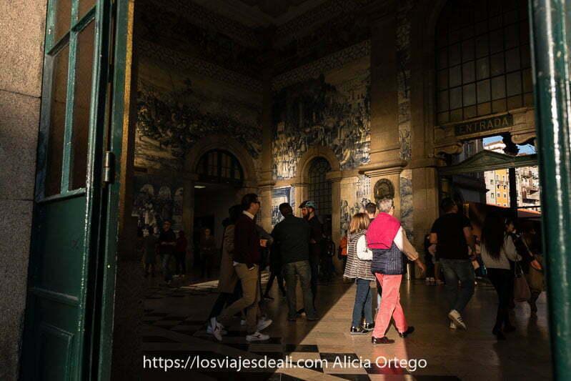 vestíbulo de la estación de são bento con sol de atardecer entrando por las puertas y gente caminando