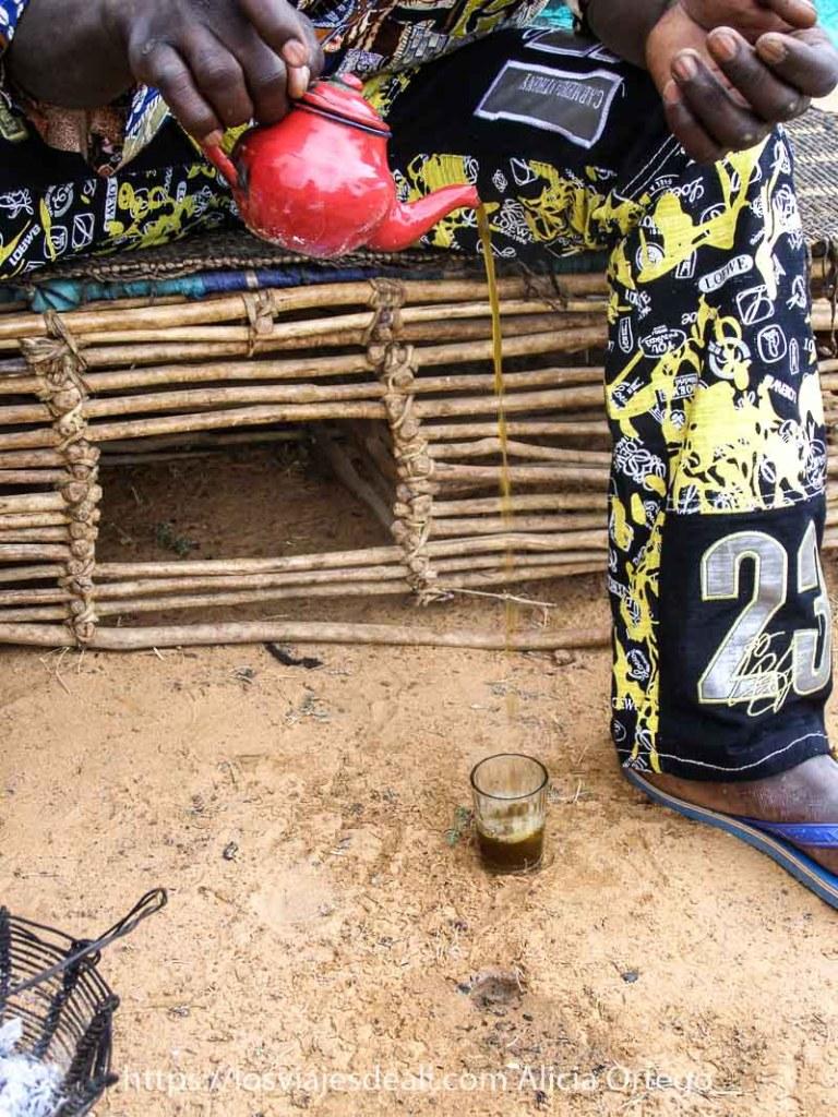 manos con una tetera roja echando té verde en un vasito de cristal puesto en el suelo en un campamento nómada de Mali