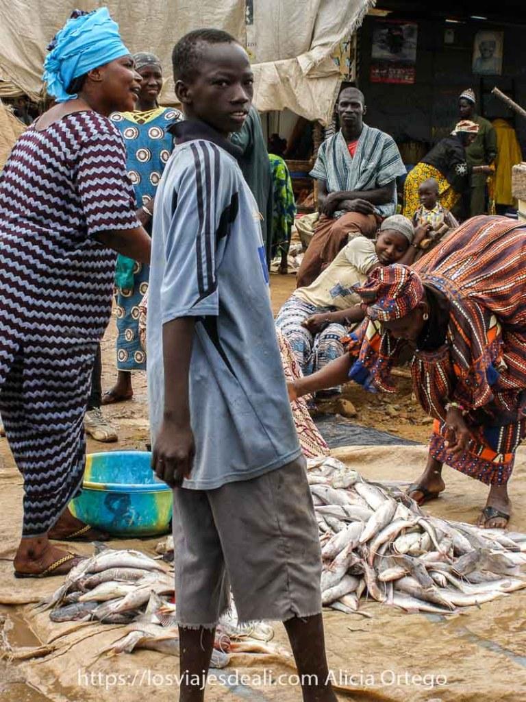 chico dándose la vuelta y detrás dos vendedoras de pescado muy expresivas