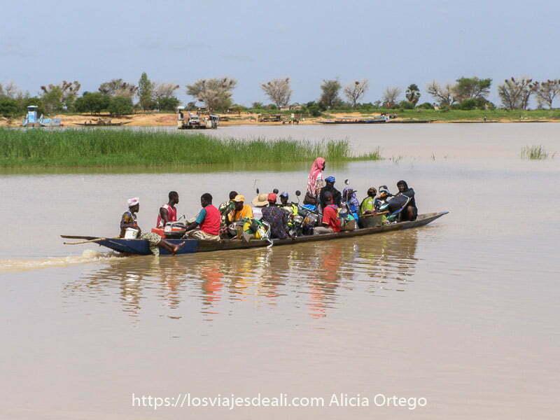 fotos de Mali: barca en el río niger plana y terminada en punta en ambos extremos llena de personas y dos motos