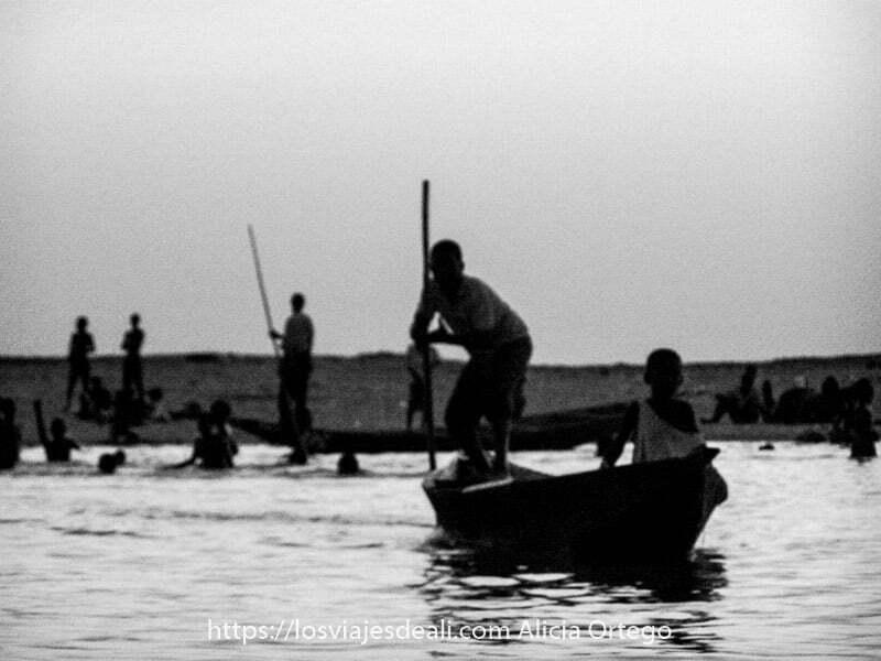 Fotos de Mali: con desenfoque dos chicos en barca empujando con una pértiga y detrás gente bañándose todos en contraste