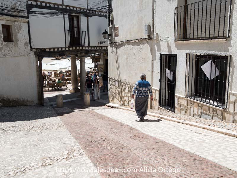 mujer andando por una calle de chinchón hacia la plaza mayor