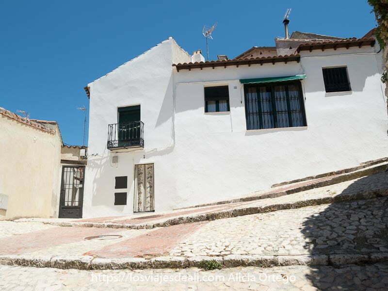 casa blanca en calle en cuesta adoquinada con cielo azul