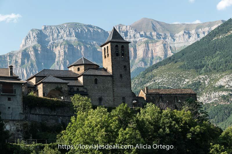 Iglesia de Torla de piedra y tejado de pizarra negra terminado en punta con las montañas de Ordesa detrás